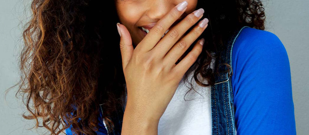 Woman hiding cold sore with her hand