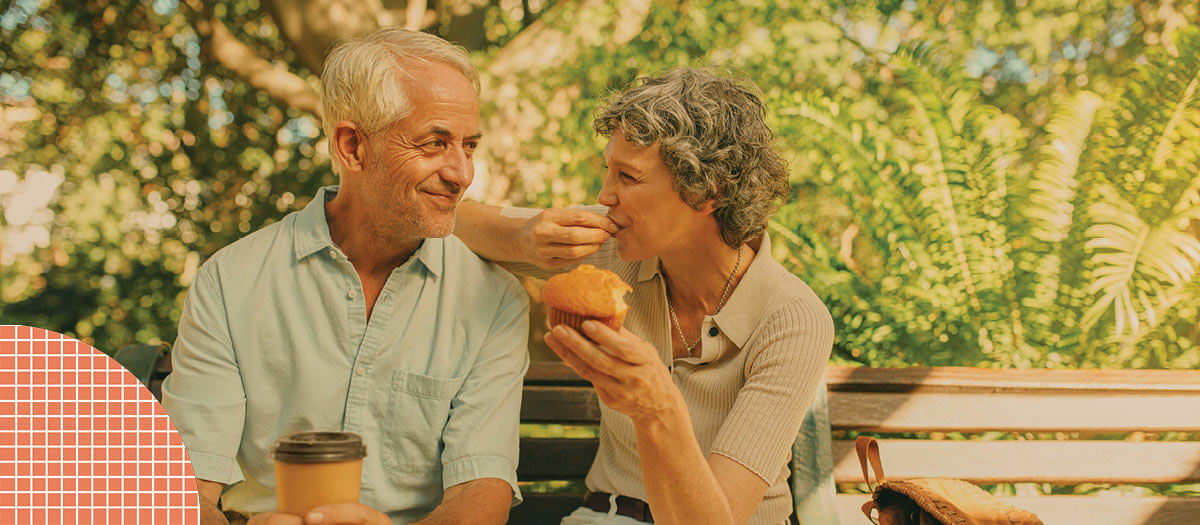 Senior couple eating breakfast on park bench