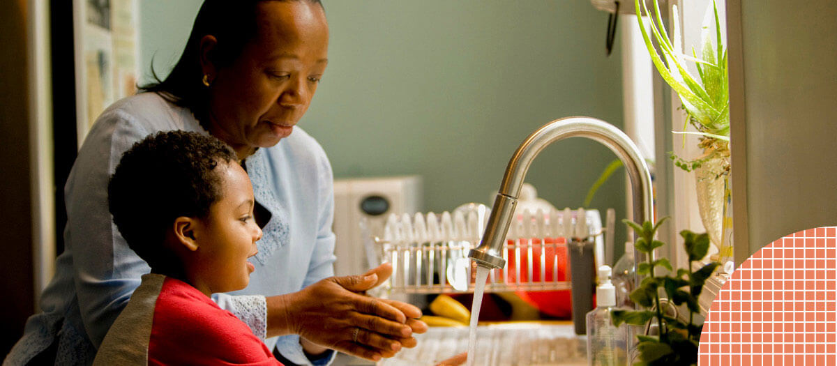 Woman washing dishes with young child