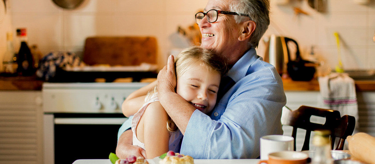 Grandma hugging granddaughter in kitchen