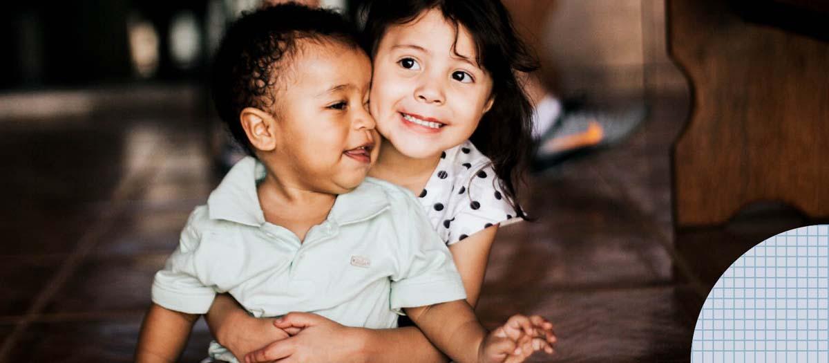 young girl hugging a toddler boy