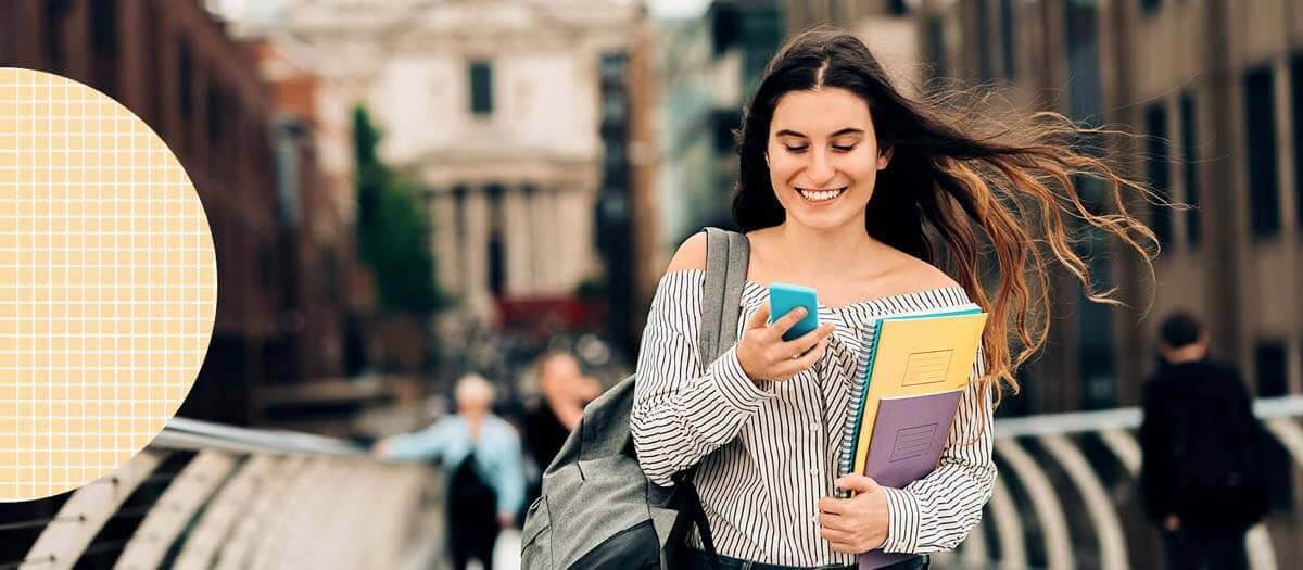 Student walking with folders and books smiling at her phone