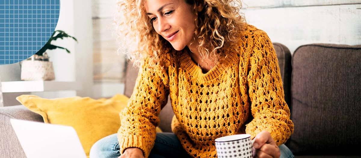 Woman in yellow sweater doing research on a laptop