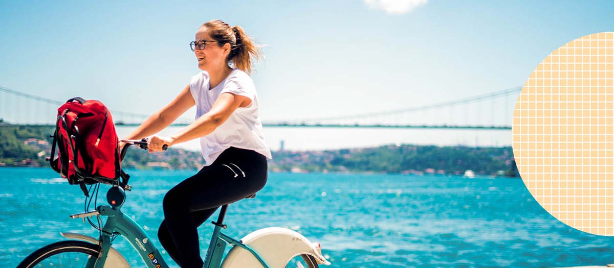 Woman riding her bike near a large body of water