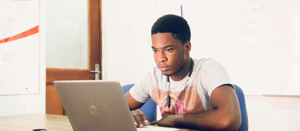 Young man looking intently at laptop