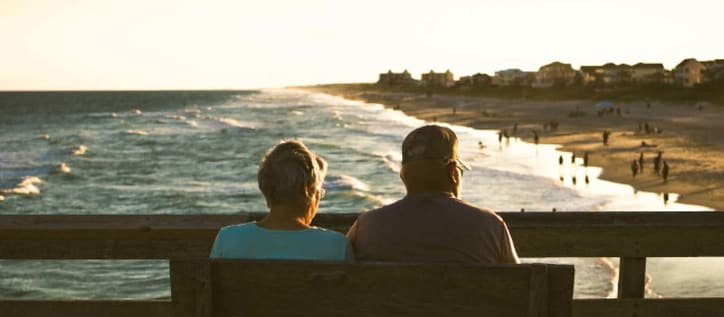 Senior couple sitting on a bench looking over the pier