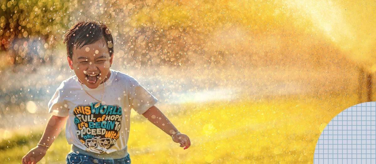 Boy running through sprinkler
