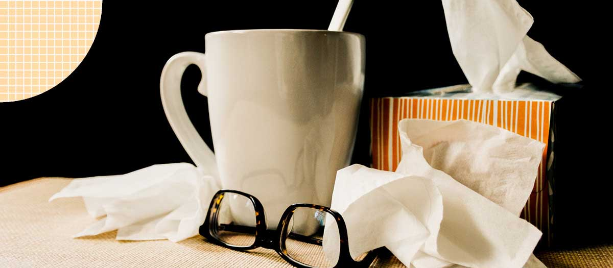 Tissues and cup of tea on bedside table
