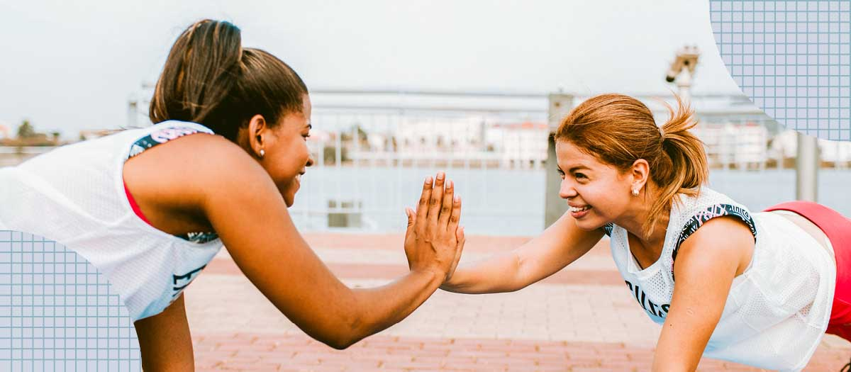 Two women high-fiving in push up position