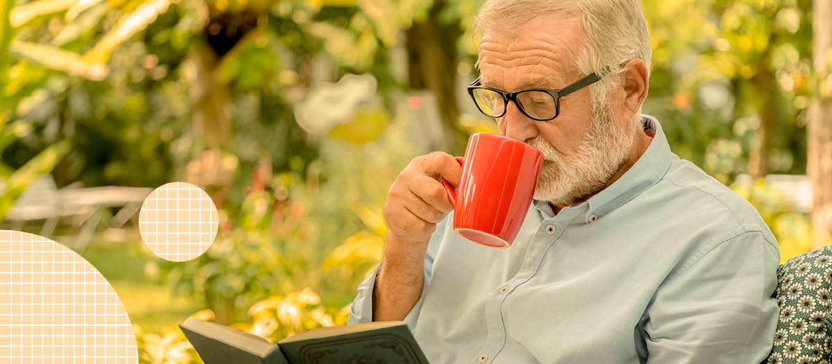 Senior man sipping coffee while reading