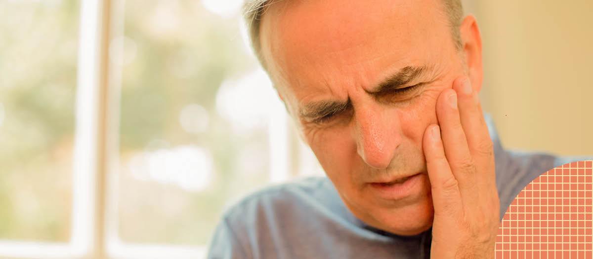 Senior man massaging his cheek