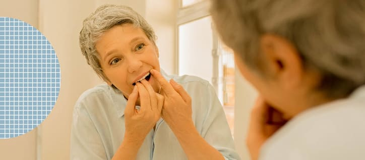 Woman flossing in bathroom mirror