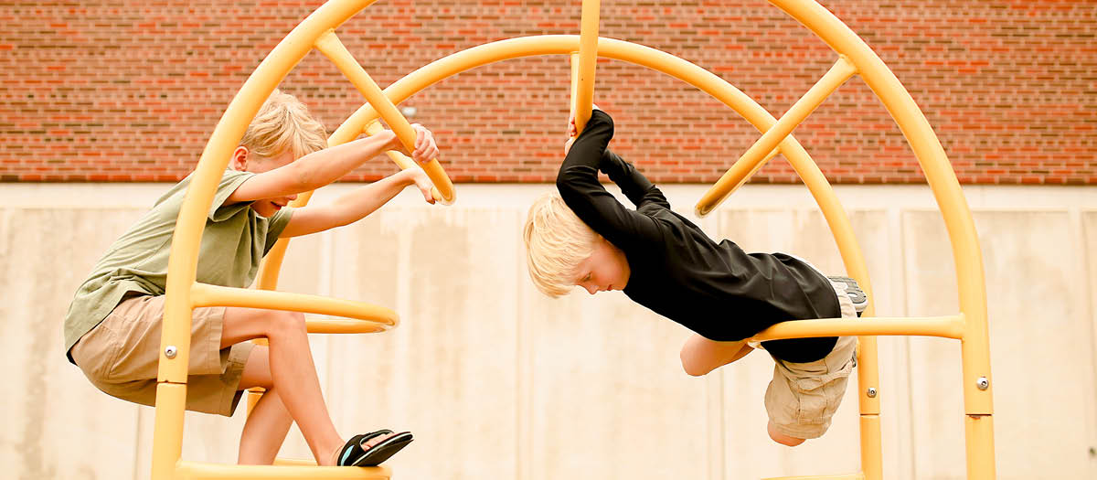 Two kids playing on a metal playground structure