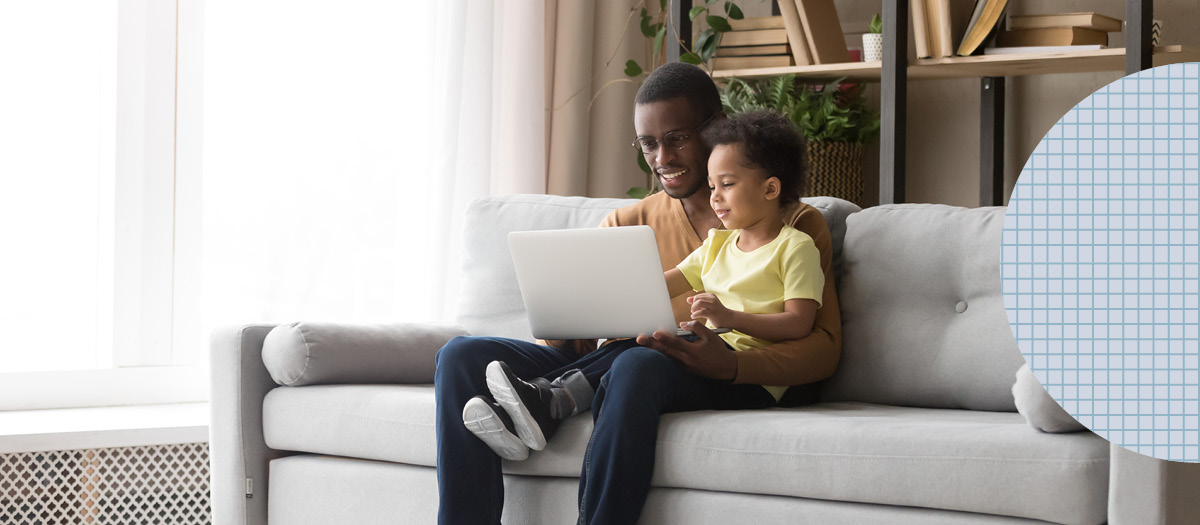 father and son smiling looking at laptop