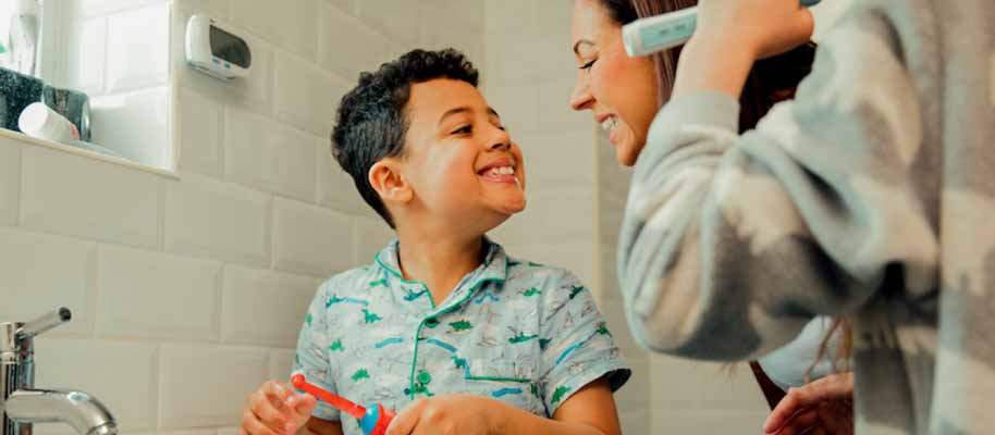 Child brushing teeth in bathroom with his mom